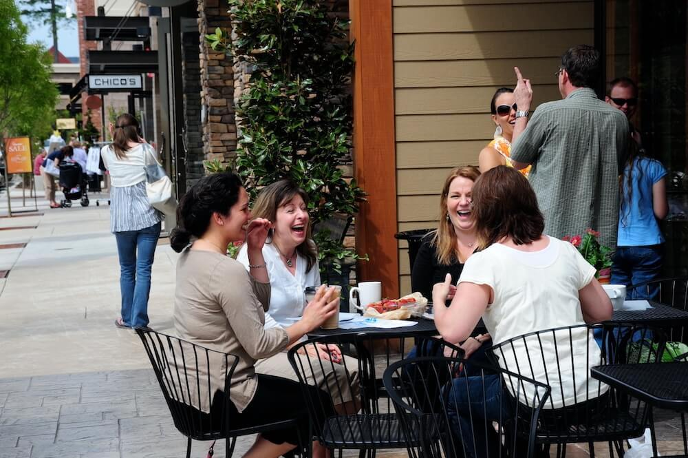 A group of women laughing while having lunch at Uptown Gig Harbor.